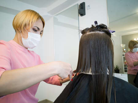 Blond hairdresser with bob haircut in medical face mask
