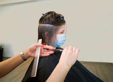 Hairdresser hands in blur motion cut female client hair in medical face mask 版權商用圖片