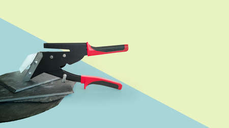 New professional tool, slate cutter, black with red handles, isolated on blue-green background, sheets of natural slate for exterior house walls, chimney and roof on the left. Horizontal banner, copy space