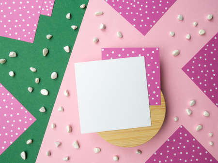 Abstract flatlay square note sheets on round wooden base, pink green diagonal paper background, corners of lilac paper with white polka dots around perimeter, scattered pebbles. Design pattern copy space