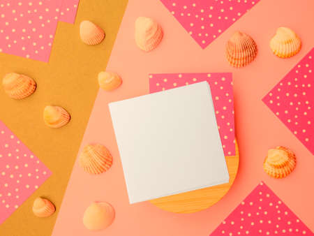 Flatlay square note sheets,wooden base,yellow beige paper, pink of white polka dots on corners,pebbles.Design copy space