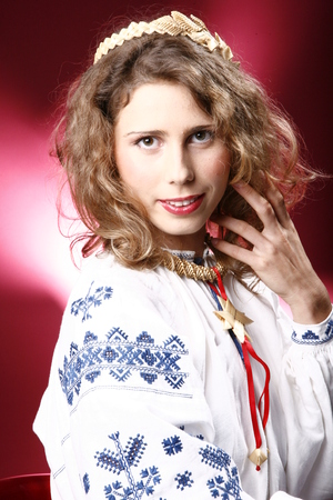 photo in ethnic clothes. The image of a young girl in a shirt that is embroidered with blue threads.