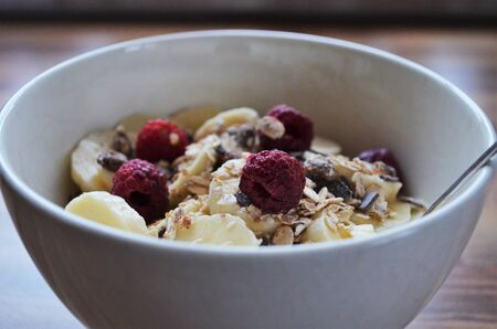 good morning breakfast, cereals in a bowl with bananas and raspberries Standard-Bild
