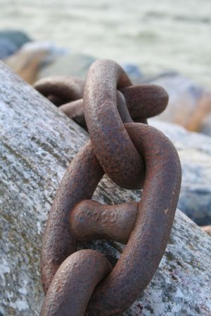 rusty chain: An old rusty chain over a log Stock Photo