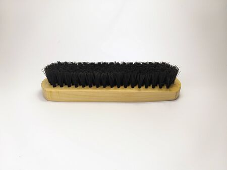 Wooden brush for cleaning clothes and shoes on a white background.