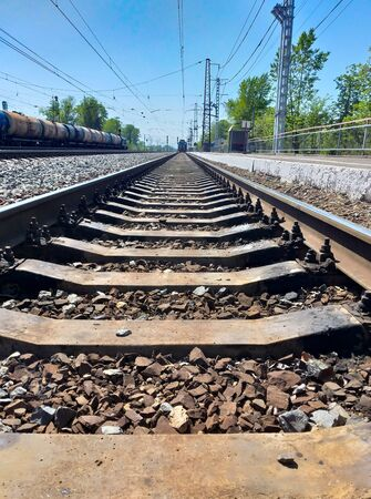 Railroad tracks at the station. Rails and sleepers. The railway is directed in perspective. Travel concept. Фото со стока