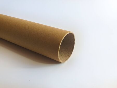 One long cardboard sleeve, pipe on a white background. Recycled beige cardboard cylinder against the background of an empty place for text.