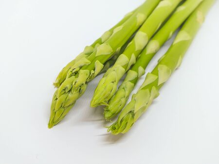 Fresh young shoots of asparagus. Sprouts of green young asparagus on a white background. Photo from above. Space for text. Banque d'images