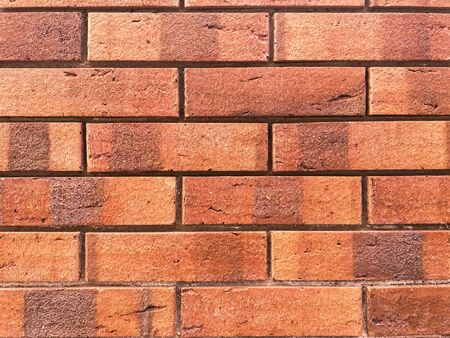 Brick wall background. Decorative brickwork from a smooth new brick. Copy space on the background of clay bricks for design work. Red brick laid in a flat masonry.