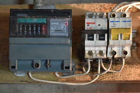 Old electricity meter and circuit breaker on a wooden substrate inside an old room under artificial lighting. Electrical safety in homes, with circuit breakers and energy meter. Home electrical system Stockfoto