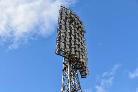 Spotlights in the stadium against the blue summer sky. Stadium lighting tower with searchlights with sky background with clouds. Tall metal lighting tower for sports arena or stadium. Bottom up view