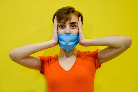 A girl with short hair, in a protective mask on her face, fearfully holds her head with her hands. Isolated on a yellow background. Concept: COVID-19, panic, protection during a pandemic.