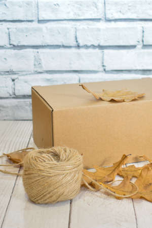 Cardboard box, autumn oak leaves and a ball of rope on the background of a wooden table top and a light brick wall. Concept: seasonal delivery, handicrafts, autumn goods. Space for text.