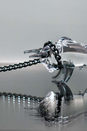 A glass figurine of a bull with a black metal chain around its neck stands against a mirrored background, looking at its reflection. Bull on a chain. Selective focus. Symbol of the year 2021