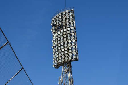 Spotlights in stadium against blue summer sky. High metal lighting tower for sports arena or stadium. Bottom up view. stadium lights reflector and dark blue sky