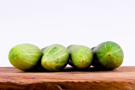 cucumis sativus: fresh green cucumbers on wooden background healthy vegetable food isolated