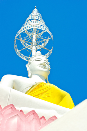 white Seated Buddha image and blue sky in the  Thai temple