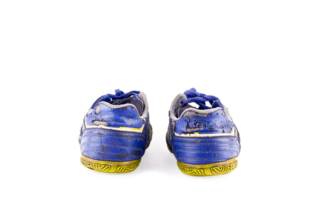 Old blue worn out futsal sports shoes on white background soccer sportware object isolated