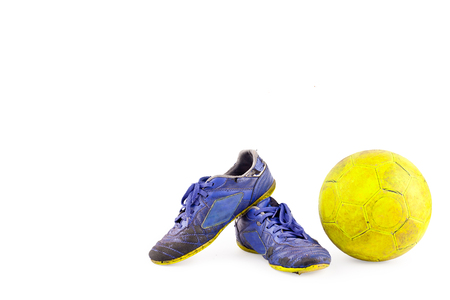 old vintage damaged futsal sports shoes and ragged yellow ball on white background football  object isolated Reklamní fotografie