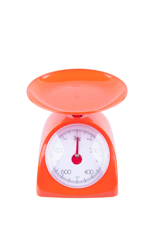 orange weighing scales with pan and dial on white background kitchen equipment object isolated