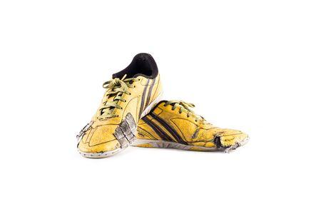 Oude gebruikte gele versleten futsal sportschoenen op een witte achtergrond voetbal sportware object geïsoleerd