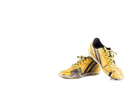 Old yellow futsal sports shoes and the insole is damaged on white background football sportware object isolated