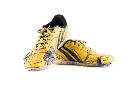 Old yellow worn out futsal sports shoes on white background soccer sportware object isolated