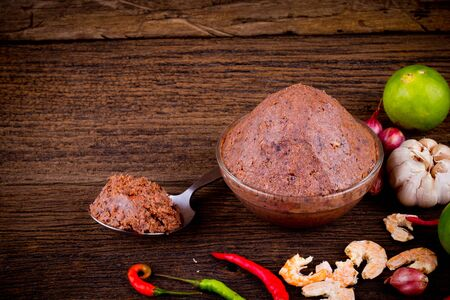 shrimp paste ( kapi ) and ingredient on brown wood texture background.