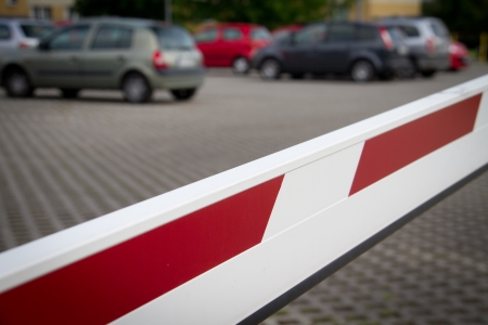 White and red barrier before the entrance to a parking lot