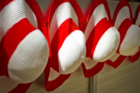 Red womans hats naging on the wall outside e shop