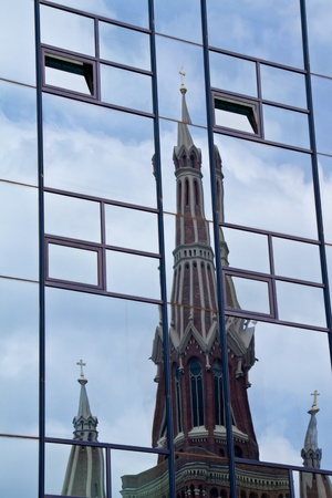 Glass office building with rflexion of a church photo