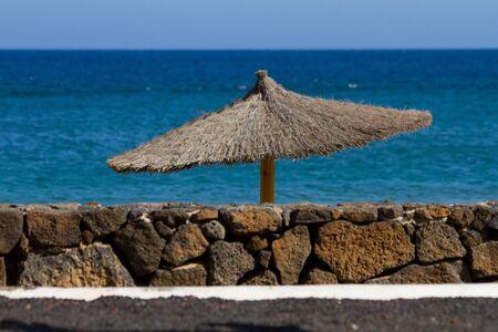 Straw beach umbrella on Lanzarote island Costa Teguise Stock Photo