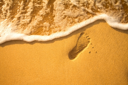 Sunset at a beach with footstep and wave