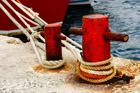 Pier with rusty bollard and mooring rope