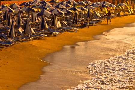 Sunset with parasols at a beach Stock Photo
