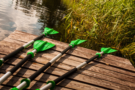 Green plastic oars lying on a pier