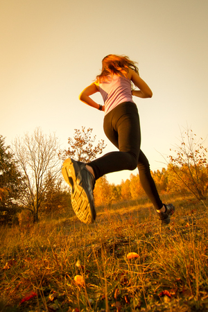 Girl running and jumping at sunset in the park natural environment