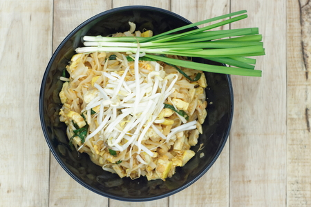 bean sprouts: Thai fried noodle in black bowl with bean sprouts and Garlic chives on topping. Pad Thai in a black bowl put on wood table.