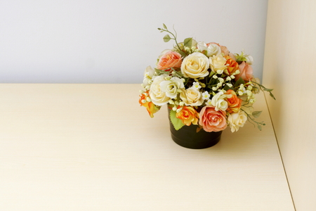 comely: Artificial flowers in flowerpot on wooded background.