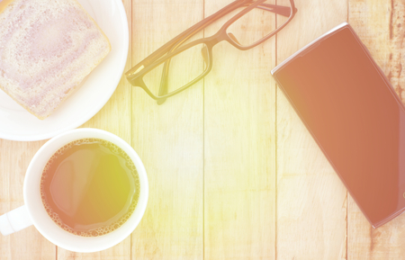 fill in: Smartphone, eyeglasses and a cup of coffee with bread on wooden background. Working in morning concept. Morning light effect fill in image. Stock Photo