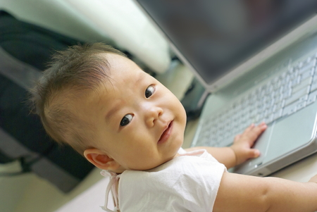 asian infant: Cute Asian baby sit on the floor. Asian infant is smiling on the floor with laptop computer. Stock Photo