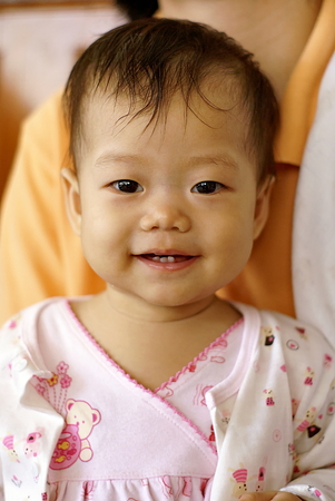 asian infant: Cute Asian infant baby in pink dress is sitting and smiling near her mom