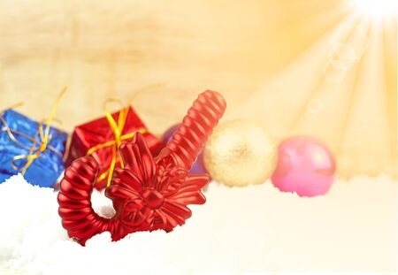 gumballs: Red Candy and Christmas decoration on white snow and wooden texture background, with sunlight rays effect in composition.