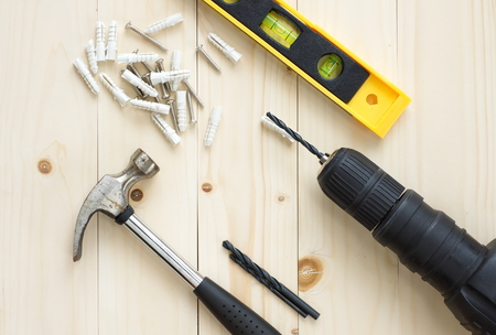 Drill and hammer, levels and screw on wooden background for DIY concepts