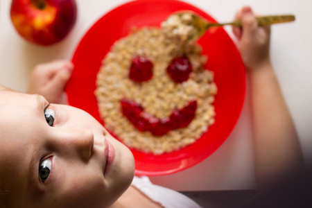 little girl eating appetizingly oatmeal from a red plate with a smiley of jam, healthy food, breakfast, childrens menu
