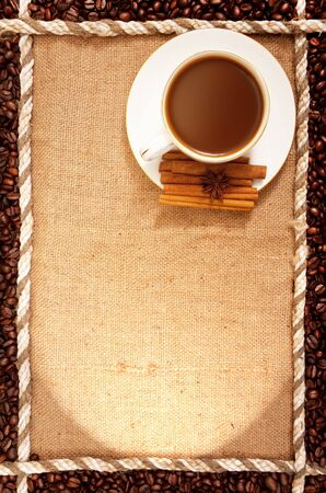 light breakfast: cup of coffee standing on sackcloth, and around the grains of roasted coffee
