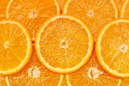 bright orange background from slices of juicy oranges photo