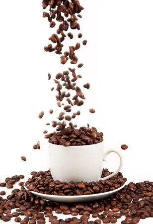 arabic coffee: pour coffee grounds into the cup is isolated on a white background Stock Photo