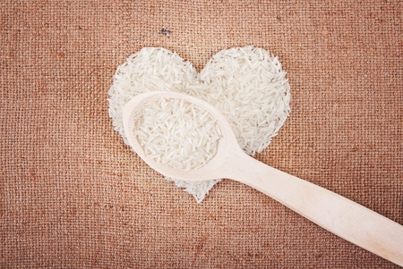 Rice laid out in a heart shape on sackcloth with a wooden spoon photo
