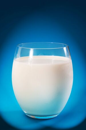glass with fresh milk on blue background photo